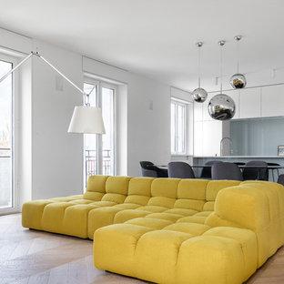 Immagine di un soggiorno minimalista di medie dimensioni e aperto con libreria, pareti bianche, pavimento in legno massello medio, TV autoportante e pavimento beige
