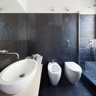 Immagine di un soggiorno minimal di medie dimensioni con pareti nere, pavimento in ardesia e pavimento nero