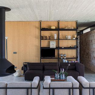 Immagine di un soggiorno minimal con pareti marroni, pavimento in cemento, camino sospeso, TV autoportante e pavimento grigio