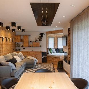 Esempio di un soggiorno rustico aperto con pareti bianche, parquet chiaro, stufa a legna e TV a parete