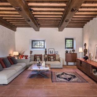 Aménagement d'un salon méditerranéen ouvert avec un mur blanc, un sol en carreau de terre cuite, aucune cheminée, aucun téléviseur, un sol orange et un plafond en poutres apparentes.