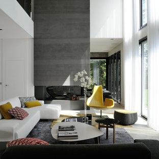 Cette photo montre un salon gris et blanc tendance ouvert et de taille moyenne avec un mur blanc, un manteau de cheminée en pierre, une cheminée double-face et aucun téléviseur.