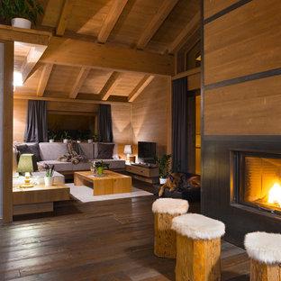 Foto di un soggiorno stile rurale chiuso con parquet scuro, camino classico, cornice del camino in legno e TV autoportante