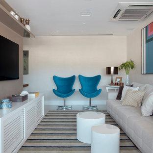 Esempio di un soggiorno design con pareti beige e TV a parete
