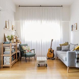 Foto di un piccolo soggiorno minimal aperto con pareti bianche, nessuna TV, libreria, nessun camino e parquet chiaro