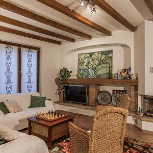Immagine di un soggiorno mediterraneo chiuso con pareti bianche, camino classico, TV autoportante e pavimento marrone
