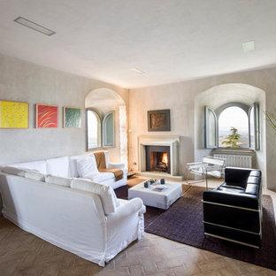 Foto di un soggiorno mediterraneo chiuso con pareti bianche, pavimento in mattoni, camino classico e cornice del camino in pietra