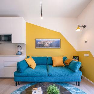 Foto di un piccolo soggiorno nordico aperto con libreria, pareti multicolore, parquet chiaro e parete attrezzata