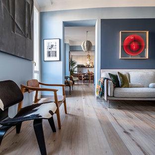 Kleine Skandinavische Bibliothek im Loft-Stil mit blauer Wandfarbe, hellem Holzboden, freistehendem TV und beigem Boden in Mailand
