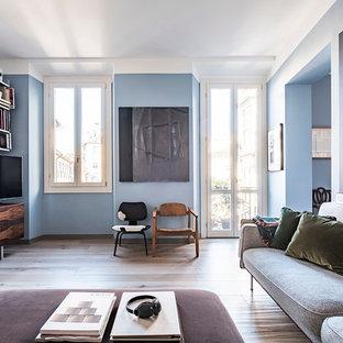 Ispirazione per un piccolo soggiorno nordico stile loft con libreria, pareti blu, parquet chiaro, TV autoportante e pavimento beige