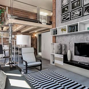 Foto di un piccolo soggiorno industriale stile loft con pareti grigie, pavimento in gres porcellanato, TV a parete e pavimento grigio