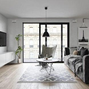 Immagine di un soggiorno scandinavo aperto con sala formale, pareti grigie, pavimento in legno massello medio, TV a parete e pavimento marrone