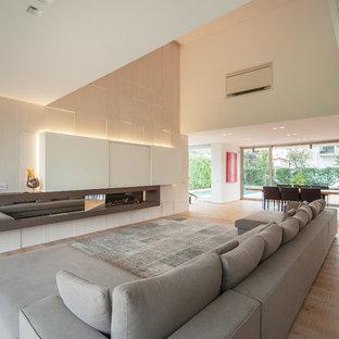 Imagen de salón abierto, moderno, grande, con paredes beige y suelo de madera clara