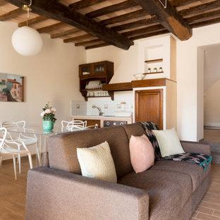 Immagine di un soggiorno mediterraneo di medie dimensioni e aperto con pareti bianche, pavimento in gres porcellanato, camino classico, cornice del camino in pietra, pavimento marrone e travi a vista