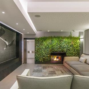 Immagine di un soggiorno contemporaneo con pareti grigie, camino bifacciale e pavimento grigio