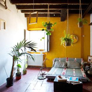 Esempio di un soggiorno mediterraneo di medie dimensioni e aperto con pavimento in terracotta, nessuna TV, pavimento rosso, pareti gialle e nessun camino