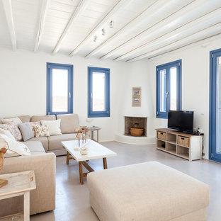 他の地域のビーチスタイルのおしゃれなオープンリビング (白い壁、コーナー設置型暖炉、レンガの暖炉まわり、据え置き型テレビ) の写真