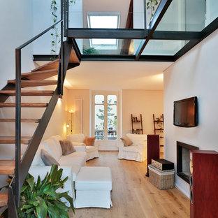 Esempio di un soggiorno tradizionale di medie dimensioni e aperto con pareti bianche, parquet chiaro, camino classico e TV a parete