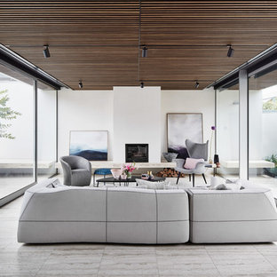 Photo of a modern open concept family room in Melbourne with white walls, a standard fireplace, a plaster fireplace surround and grey floor.