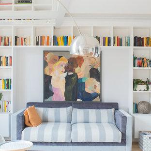 Immagine di un soggiorno scandinavo con libreria, pareti bianche e TV autoportante