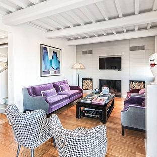 Immagine di un soggiorno mediterraneo aperto con pareti bianche, pavimento in legno massello medio, camino classico e TV a parete