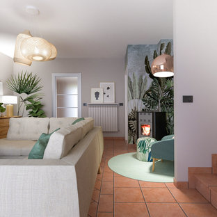 中くらいのコンテンポラリースタイルのおしゃれな独立型リビング (ライブラリー、マルチカラーの壁、テラコッタタイルの床、薪ストーブ、金属の暖炉まわり、埋込式メディアウォール、ピンクの床) の写真