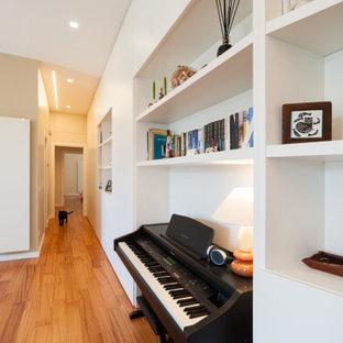 Modelo de biblioteca en casa abierta, moderna, grande, con paredes beige, suelo de madera clara, chimeneas suspendidas, televisor independiente y suelo rojo