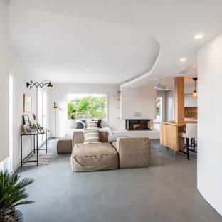 Idee per un soggiorno stile marino di medie dimensioni e aperto con pareti bianche, pavimento in cemento, camino ad angolo, cornice del camino in intonaco e pavimento grigio