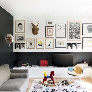 Idee per un soggiorno scandinavo chiuso con pareti nere, parquet chiaro e TV autoportante