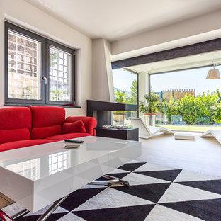 Immagine di un ampio soggiorno minimal aperto con pareti bianche, parquet chiaro, camino bifacciale e cornice del camino in metallo