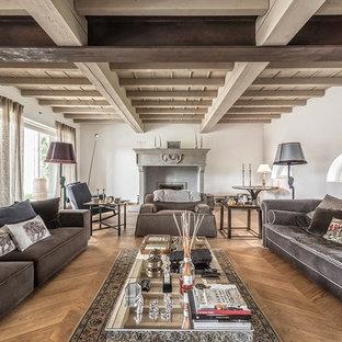 Idee per un soggiorno mediterraneo aperto con sala formale, pareti bianche, pavimento in legno massello medio, camino classico, cornice del camino in cemento e pavimento marrone
