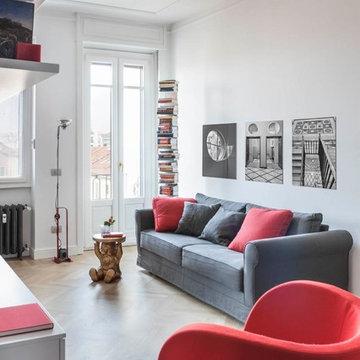 Particolare zona living arredata in grigio e rosso. Parquet in massello di rover