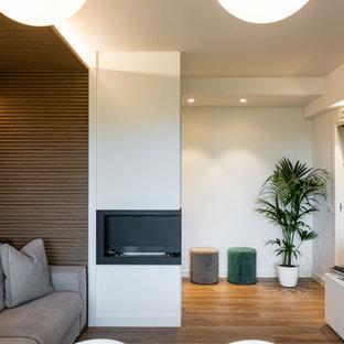 Mittelgroßes, Repräsentatives, Abgetrenntes Modernes Wohnzimmer mit weißer Wandfarbe, Porzellan-Bodenfliesen, Kamin, Kaminumrandung aus Metall, Multimediawand, braunem Boden, Holzdielendecke und vertäfelten Wänden in Mailand