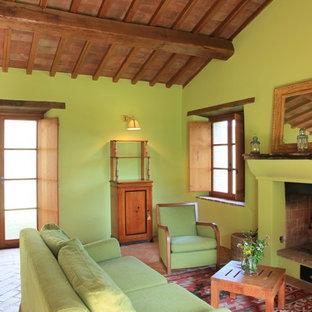 Ispirazione per un soggiorno mediterraneo aperto con pareti verdi, pavimento in terracotta, camino classico, cornice del camino in intonaco e nessuna TV