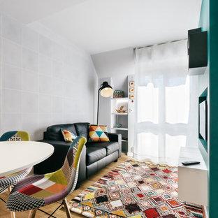 Immagine di un piccolo soggiorno design aperto con pareti grigie, parquet chiaro, TV a parete e pavimento beige
