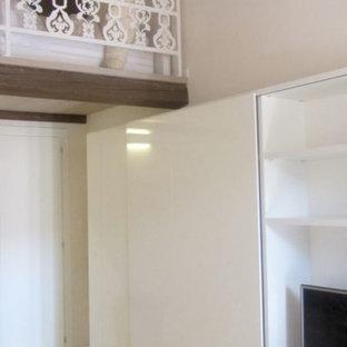 Kleines Modernes Wohnzimmer mit weißer Wandfarbe, Betonboden, verstecktem TV, weißem Boden und Holzdecke in Bologna