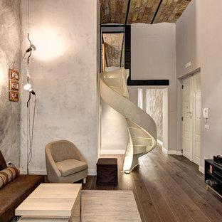 ローマのインダストリアルスタイルのおしゃれなファミリールーム (グレーの壁、濃色無垢フローリング) の写真