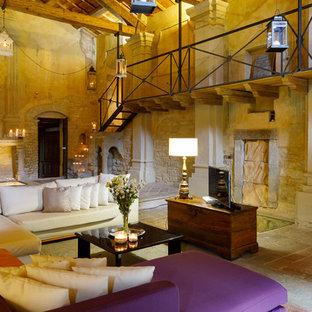 Immagine di un soggiorno in campagna aperto con libreria, pareti beige, TV autoportante e pavimento beige