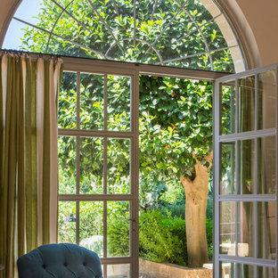 Immagine di un grande soggiorno mediterraneo aperto con pareti beige, pavimento in pietra calcarea, camino classico, cornice del camino in legno e pavimento beige