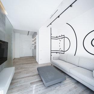 Esempio di un soggiorno minimalista con pareti multicolore, parquet chiaro, nessun camino e TV a parete