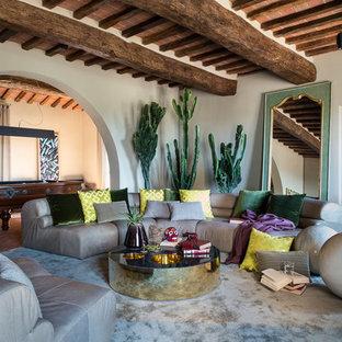 Immagine di un ampio soggiorno mediterraneo aperto con pareti beige e pavimento in mattoni