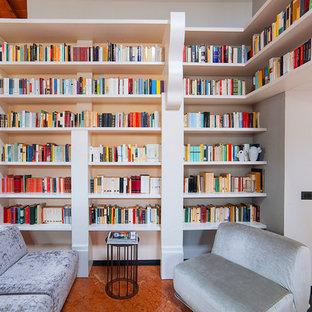 Esempio di un soggiorno mediterraneo con libreria, pareti bianche e pavimento marrone