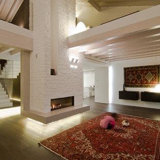 Foto di un ampio soggiorno design aperto con pareti bianche, parquet scuro, camino classico e cornice del camino in pietra