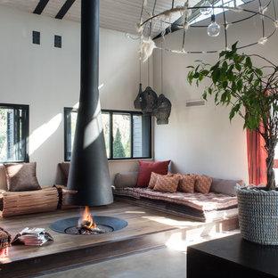 Ispirazione per un soggiorno industriale stile loft con camino sospeso e pavimento grigio