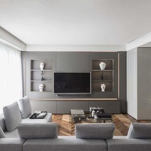 Exempel på ett modernt vardagsrum, med grå väggar, mellanmörkt trägolv, en inbyggd mediavägg och brunt golv