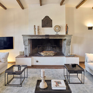 Inspiration for a medium sized mediterranean family and games room in Florence with white walls, medium hardwood flooring, a standard fireplace, a wall mounted tv, brown floors and a stone fireplace surround.