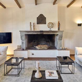 Immagine di un soggiorno mediterraneo di medie dimensioni con pareti bianche, pavimento in legno massello medio, camino classico, TV a parete, pavimento marrone e cornice del camino in pietra