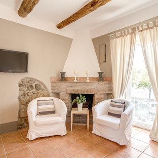 Foto di un piccolo soggiorno country con pareti beige, pavimento con piastrelle in ceramica, camino ad angolo, cornice del camino in mattoni e TV a parete