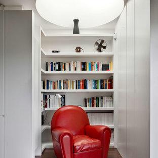 Imagen de sala de estar con biblioteca actual, pequeña, sin chimenea, con paredes blancas y suelo de madera oscura