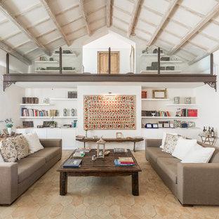 Esempio di un grande soggiorno mediterraneo aperto con libreria, pareti bianche, pavimento in terracotta e nessuna TV